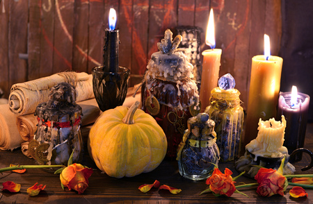 Old paper scrolls, pumpkin, candles and magic bottles on witch table. Wicca, esoteric, Halloween and occult background with vintage magic objects for mystic rituals