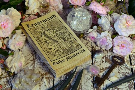 Still life with Lenormand tarot cards deck and roses. Esoteric, wicca and occult background, fortune telling and divination ritual with tarot cards. 免版税图像