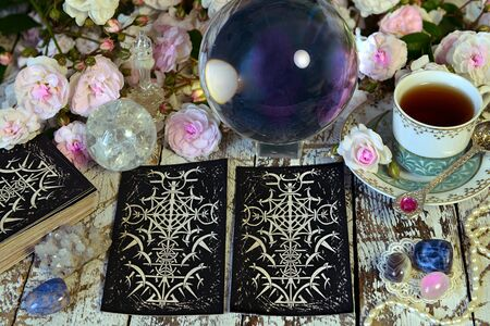 Still life with tarot cards, cup and crystal. Esoteric, wicca and occult background, fortune telling and divination ritual with tarot cards.