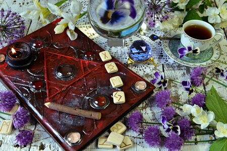 Magic book grimoire with runes, flowers, crystals and mystic objects on witch table. Esoteric, gothic and occult concept, Halloween mystic background, divination ritual