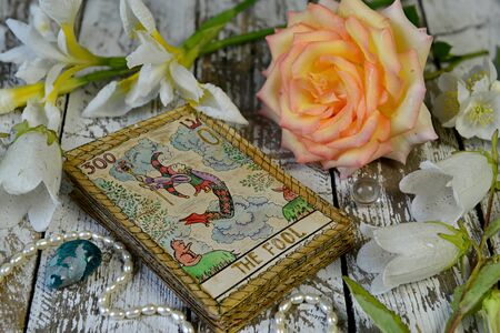 Tarot cards and flowers on witch wooden altar. Esoteric, gothic and occult concept, Halloween mystic background, divination ritual Stok Fotoğraf