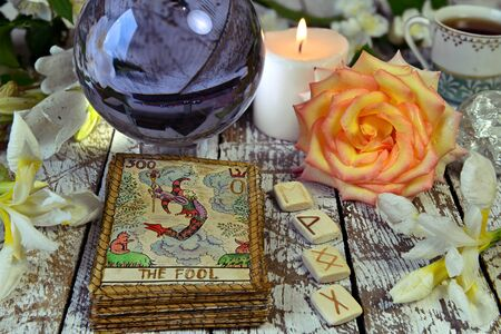Tarot cards deck, crystal ball, runes and flowers on witch table. Esoteric, gothic and occult concept, Halloween mystic background, divination ritual Stok Fotoğraf