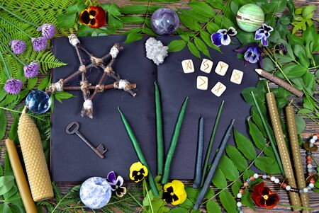 Magical objects with pentagram, open book, healing crystals, runes and candles on witch table. Esoteric, gothic and occult concept, Halloween mystic background, divination ritual