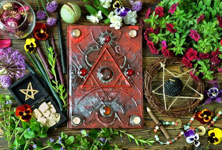 Still life with magical book, healing crystals, runes and herbs on witch table. Esoteric, gothic and occult concept, Halloween mystic background, divination ritual