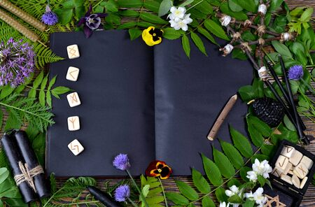 Open witch book with black pages, copy space, runes, herbs and black candles on table. Esoteric, gothic and occult concept, Halloween mystic background, divination ritual