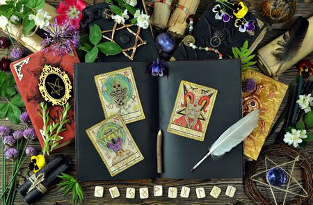 Tarot cards, open grimoire book and magic objects on witch table. Esoteric, gothic and occult concept, Halloween mystic background, divination ritual