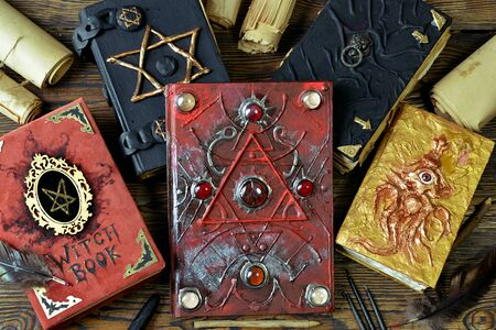 Pile of magical evil books with spells on witch table. Esoteric, gothic and occult concept, Halloween mystic background, divination ritual Stok Fotoğraf
