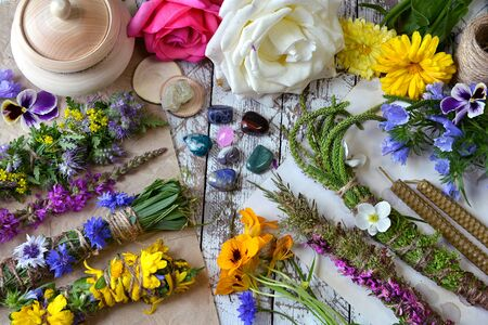 Top view of witchery scrolls with magic herbs, summer flowers and crystals on table. Esoteric, occult and mystic concept, alternative medicine background with natural healing ingredients.