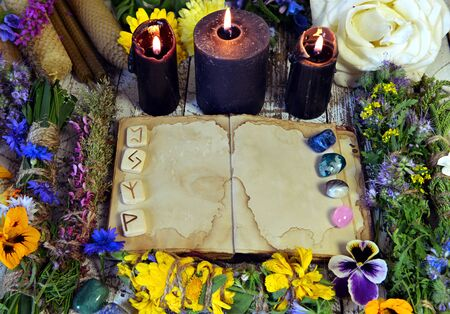 Open book with empty pages, black candles, reiki crystals and herbs on witch table. Esoteric, occult and mystic concept, alternative medicine background. 스톡 콘텐츠