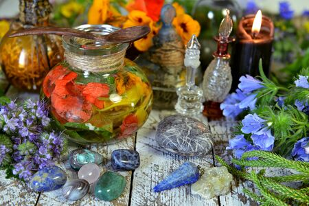 Still life with green witch herbs, potion, crystals and candles. Esoteric, occult and mystic concept, alternative medicine background with natural healing ingredients.