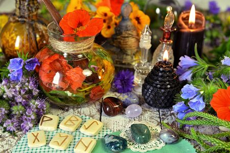 Still life with reiki crystals, runes, black candles and witch herbal potions on table. Esoteric, occult and mystic concept, alternative medicine background with natural healing ingredients.