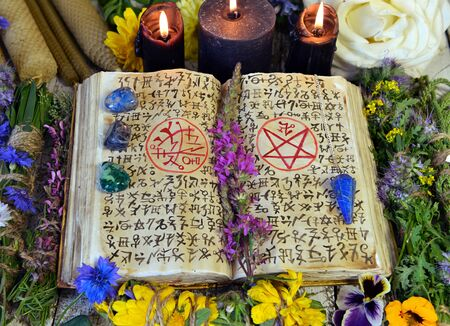 Witch book with spells and magic symbols, black candles, reiki crystals and flowers. Esoteric, occult and mystic concept. No foreign language, text is fantasy one.
