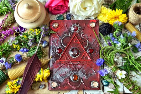 Decorated magic book, quill, summer herbs and flowers on witch table. Esoteric, occult and mystic concept, alternative medicine background with natural healing ingredients. 스톡 콘텐츠