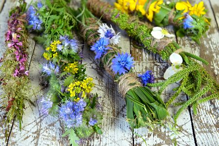 Herbal scrolls with summer plants and flowers on witch table. Esoteric, occult and mystic concept, alternative medicine background with natural healing ingredients.