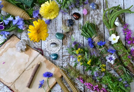 Still life with calendula flowers, herbs, reiki crystals on witch table. Esoteric, occult and mystic concept, alternative medicine background with natural healing ingredients.