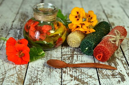 Candles and glass bottle with healing potion of nasturtium flowers. Esoteric, occult and mystic concept, alternative medicine background with natural healing ingredients.