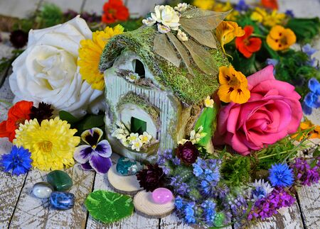 Tiny adorable fairy house with beautiful rose, viola, nasturtium and viola flowers and crystals. Greeting cards, birthday, love and romantic concept. Vintage summer background
