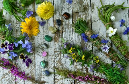 Top view of herbs, flowers and reiky crystals on wooden witch table. Esoteric, occult and mystic concept, alternative medicine background with natural healing ingredients.