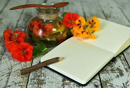 Nasturtium flowers in glass bottle and open diary with pencil on wooden table. Esoteric, occult and mystic concept, alternative medicine background with natural healing ingredients.