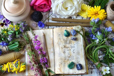 Witch spell book, calendula, rose flowers, reiki crystals and candles on wooden table. Esoteric, occult and mystic concept, alternative medicine background with natural healing ingredients.