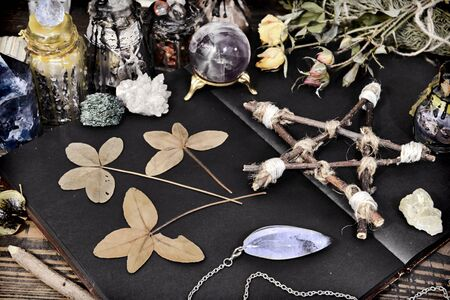 Creepy still life with open book, pentagram, four-lead clover and crystals on witch table. Esoteric, wicca and occult background, fortune telling and divination ritual, mystic concept Foto de archivo - 137412054