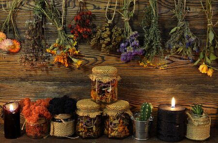 Still life with dry flowers and herbs, witch bottles, black candle and moss in jar. Esoteric, wicca and occult background, fortune telling and divination ritual, mystic concept Foto de archivo - 137412058