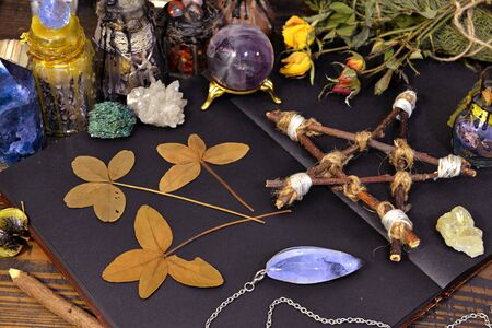 Pentagram, open diary, four-leaf clover and gemstone with herbs on witch table. Esoteric, wicca and occult background, fortune telling and divination ritual, mystic concept Foto de archivo - 137412065