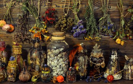 Witch laboratory with potion, elixirs, glass bottles, dry flowers, herbs and ingredients. Esoteric, wicca and occult background, fortune telling and divination ritual, mystic concept Foto de archivo - 137412060