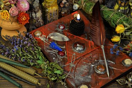 Still life with magic book, black candle, quill, herbs and elixir on witch table. Esoteric, wicca and occult background, fortune telling and divination ritual, mystic concept Foto de archivo - 137412061
