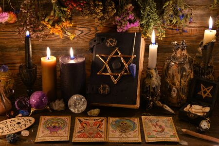 Still life with pentagram book, burning candle, crystal gemstone and tarot cards on witch table. Esoteric, wicca and occult background, fortune telling and divination ritual, mystic concept