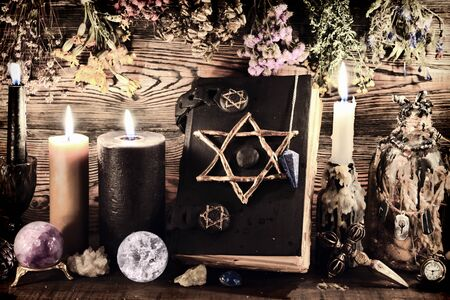 Creepy still life with burning candles, pentagram book, elixir bottles and dry herbs on witch table. Esoteric, wicca and occult background, fortune telling and divination ritual, mystic concept