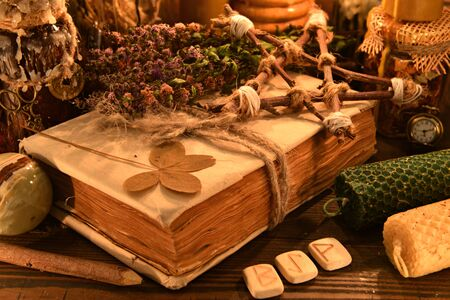 Old book with four-leaf clover, candles, herbs and runes on witch table. Esoteric, wicca and occult background, fortune telling and divination ritual, mystic concept