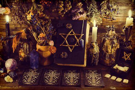 Libro de brujas espeluznante con pentagrama, cartas del tarot, runas, piedras preciosas, velas y objetos mágicos. Esotérico, wicca y trasfondo oculto, adivinación y ritual de adivinación, concepto místico Foto de archivo