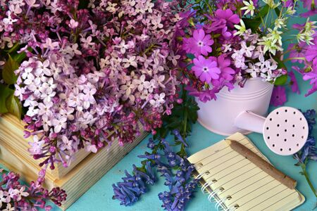 Lilac and spring flowers with diary book and watering can on working table. Vintage gardening concept, home hobby still life Foto de archivo - 137412063
