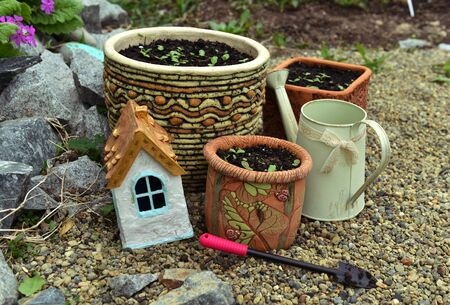 Decorative tiny house with flowerpots with seedlings and working took outside in the garden. Vintage botanical background with plants, home hobby still life with gardening and planting objects Foto de archivo - 137412067