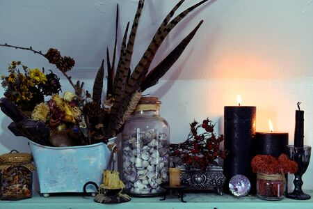 Black candles, feathers and shells in glass jar on the shelf. Esoteric, wicca and occult background, fortune telling and divination ritual, mystic concept