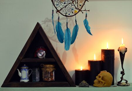 Black candles, skull, dreamcatcher and other ritual objects.  Esoteric, wicca and occult background, fortune telling and divination ritual, mystic concept