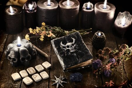 Runes, old diabolic book and black burning candles on witch table. Wicca, esoteric and occult background with vintage magic objects for mystic rituals. Halloween and gothic concept Foto de archivo
