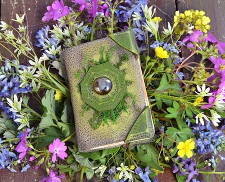 Top view of green witch book on wildflowers. Vintage background with old book and flowers, romantic concept