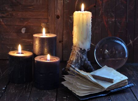 Creepy still life with burning candles, crystal ball and open diary on witch table. Esoteric, wicca and occult background with magic objects, fortune telling and divination ritual, Halloween mystic background. Banque d'images