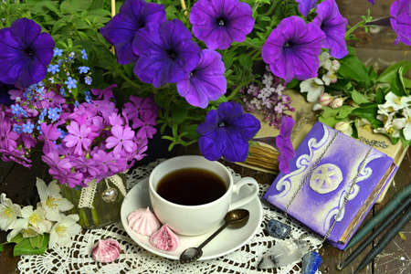 Cup of tea with petunia flowers and books on table. Esoteric, gothic and occult background with magic objects, mystic and fairy tale concept
