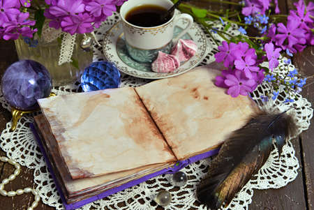 Cozy still life with open diary with blank pages, crystal, primrose flowers and cup of tea on table. Esoteric, gothic and occult background with magic objects, mystic and fairy tale concept Stock fotó