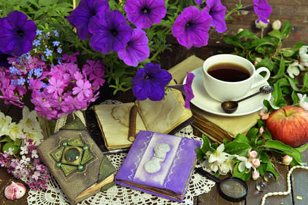 Romantic still life with petunia bouquet, decorated diary and cup of tea. Esoteric, gothic and occult background with magic objects, mystic and fairy tale concept Stock fotó
