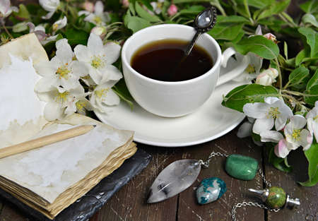 Cup of tea with open diary and apple tree flowers on planks. Esoteric, gothic and occult background with magic objects, mystic and fairy tale concept Stock fotó