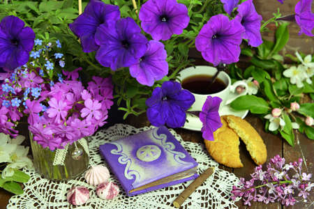Decorated book with petunia bunch and cup of tea on wooden table. Esoteric, gothic and occult background with magic objects, mystic and fairy tale concept Stock fotó