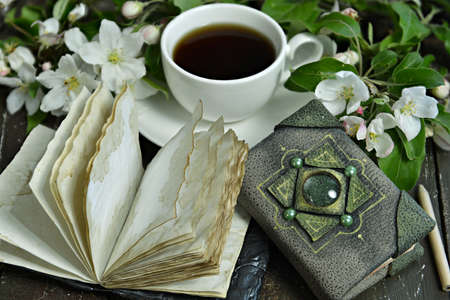 Open diary book with cup of tea and blooming apple tree branches on table. Esoteric, gothic and occult background with magic objects, mystic and fairy tale concept