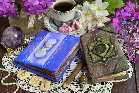 Decorated book and diary with cup of tea and flowers on green witch table. Esoteric, gothic and occult background with magic objects, mystic and fairy tale concept Stock fotó
