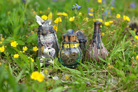 Witch bottles with potion and elixir on the grass in the spring garden. Esoteric, gothic and occult background with magic objects, mystic and fairy tale concept