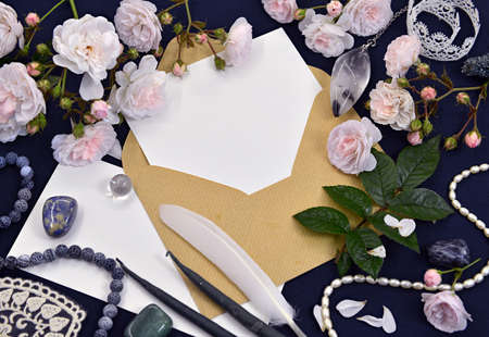 Envelope with paper letter, quill, rose and decorations on table. Mystic and romantic background with copy space and blank, vintage romantic concept for mock up, top view 版權商用圖片