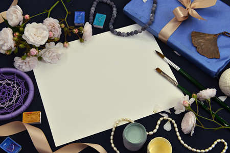 White paper sheet with book, rose flowers and artistic objects. Mystic and romantic background with copy space and blank, vintage romantic concept for mock up, top view 版權商用圖片